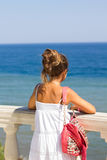 Girl and the Sea. A young girl in a white dress looks at the sea on a bright sunny day Stock Photo