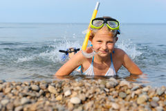 The girl on seacoast flounders about in water Royalty Free Stock Photos
