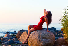 Girl on seacoast before a sunset Royalty Free Stock Images
