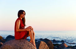 Girl on seacoast before a sunset Stock Photos