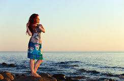 Girl on seacoast before a sunset Stock Photo