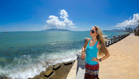 A girl on the seafront at nha trang bay. With pearl island resort in the background royalty free stock image