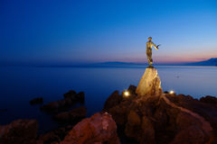 Girl with seagull. In the evening on the Adriatic coast in Opatija in Croatia with Cres island in the background Stock Photography