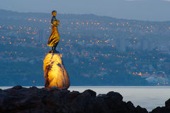 Girl with Seagull with Rijeka in the Background. Girl with seagull in the dawn on the Adriatic coast in Opatija in Croatia with Port of Rijeka in the background Stock Photo