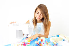 Girl seamstress and sewing machine Stock Images