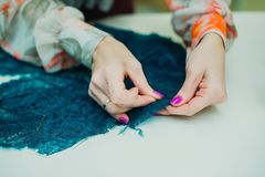 Girl seamstress working in his Studio.Learning to sew stock photo