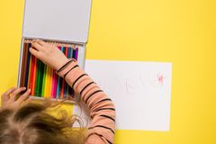 Girl searching for a color pencil. Girl is selecting out of a pencil box a other color Royalty Free Stock Photography