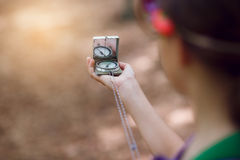 Girl searching direction with a compass in the forest Stock Photos