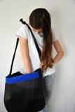 Girl searching something in handbag. Teenage girl searching something in her shoulder bag stock images