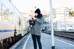 Girl searching something in her bag and standing next to a train Stock Photos