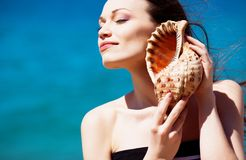 Girl with seashell. Beautiful girl with seashell in hands and blue sea water background Royalty Free Stock Image
