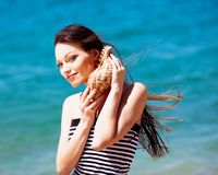 Girl with seashell. Beautiful girl with seashell in hands on the beach Stock Photo