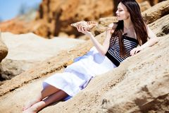 Girl with seashell. Beautiful girl with seashell in hands lying on the big stone Royalty Free Stock Images