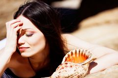 Girl with seashell. Beautiful girl with seashell lying on the stone under the summer sun Stock Photography