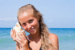 Girl with a seashell on the sea. A girl holds a shell in his hands on the beach Stock Photos