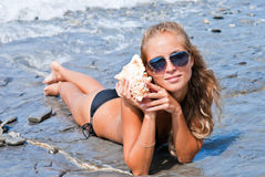 Girl with a seashell on the sea. A girl holds a shell in his hands on the beach Royalty Free Stock Photos
