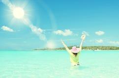 Girl with a seashell in the turqouise. Water of Atlantic. Exuma, Bahamas Stock Image