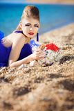 Girl with seashells on the beach Stock Photography