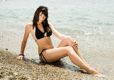 Girl on seashore. Young brunette woman sitting on wet pebble looking at camera smiling Royalty Free Stock Images