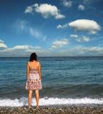Girl at the seashore. A beautiful girl staying at the seashore Royalty Free Stock Images