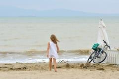 Girl on the seashore. Bike on the sand Stock Image