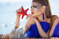 Girl with seastar on the beach royalty free stock photos