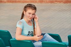 The girl on the seat in the stands.Girl loves to listen to the song in the phone. Closeup portrait of a sporty teen girl Stock Image