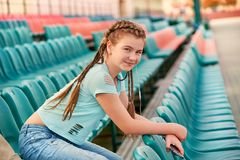 The girl on the seat in the stands.Girl loves to listen to the song in the phone. Teenage girl sitting at the stadium in the blue shirt.The stands soft focus Royalty Free Stock Image