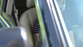 Girl seated in a car listening to her music. Girl seated in the front passenger seat of a car listening to her music on headphones viewed through the windscreen stock video footage