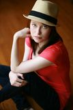 Girl seated in hat Stock Photo