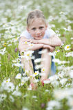 Girl seated in meadow between daisies Royalty Free Stock Photos