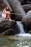 Girl seated on a rock fishing Stock Photography