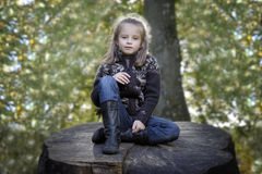 Girl seated on a trunk in the park Royalty Free Stock Photography