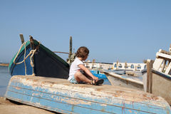 The girl seats on the boat Royalty Free Stock Image