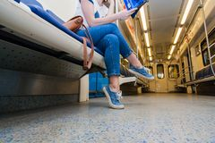 Girl seats in empty subway train. She is in blue jeans and white t-short stock images