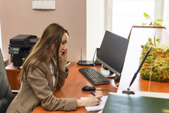 Girl Secretary works in the office, a lot of talking on the phone. hard work. Stock Photography