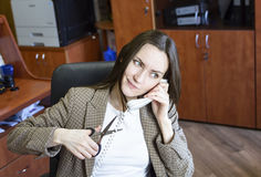 Girl Secretary works in the office, a lot of talking on the phone. hard work. Royalty Free Stock Image