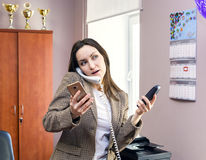 Girl Secretary works in the office, a lot of talking on the phone. hard work. Stock Image