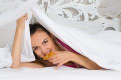 Girl secretly enjoying a croissant Royalty Free Stock Images