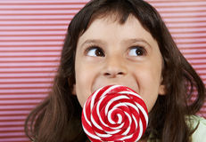 Girl secretly enjoys a large lollipop. Royalty Free Stock Photography