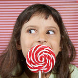 Girl secretly enjoys a large lollipop. Royalty Free Stock Images