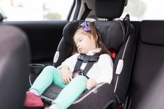 Girl Secured With Seat Belts Resting In Car. Adorable sweet girl sleeping peacefully on safety seat in car royalty free stock images