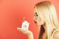 Girl or seductive blonde woman hold small white gift box royalty free stock photography