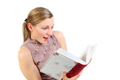 Girl seeing an exciting picture. Blonde girl looking excited on a photo in a photoalbum Stock Image