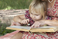 Girl sees something in books featuring mom Stock Photo