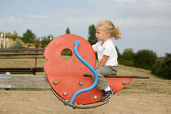 Girl on seesaw stock photography