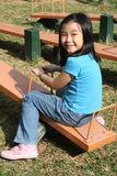Girl on seesaw. Happy girl playing seesaw at the playground in the park on sunny day Stock Photos