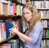 Girl selecting book from a bookshelf in the library Royalty Free Stock Images