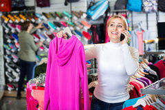 Girl selecting cardigan and chatting on the phone Royalty Free Stock Photography