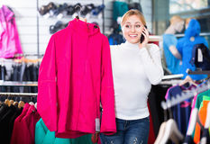 Girl selecting cardigan and chatting on the phone Stock Image